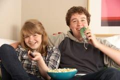 夫妇坐的沙发少年电视注意 库存图片