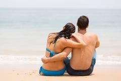 夫妇坐的海滩 免版税库存照片