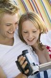 年轻夫妇坐看摄象机屏幕关闭的沙发  库存图片