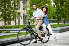 年轻夫妇坐自行车 免版税库存图片