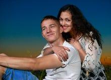 年轻夫妇坐草和容忍在室外的国家,黑暗的夜空,爱概念,浪漫人民 库存照片