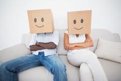 夫妇坐长沙发与箱子一起在头顶上 库存图片