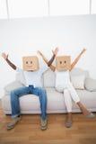 夫妇坐长沙发与箱子一起在头顶上 免版税库存图片