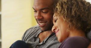 黑夫妇坐长沙发微笑 免版税库存图片
