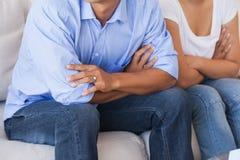 夫妇坐长沙发 库存照片