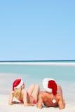 夫妇坐戴圣诞老人帽子的海滩 免版税库存图片