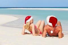 夫妇坐戴圣诞老人帽子的海滩 库存图片