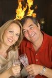夫妇壁炉愉快敬酒 免版税库存照片