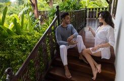 年轻夫妇大阳台热带旅馆、男人和妇女热带假日假期 免版税图库摄影