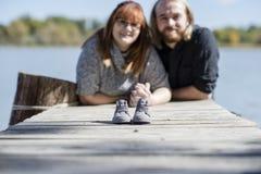 夫妇宣布与一双微小的鞋的婴孩公告 免版税库存照片