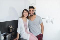 年轻夫妇容忍在厨房、西班牙人和亚洲妇女拥抱里 库存照片