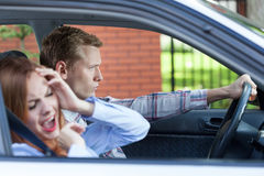 年轻夫妇尖叫在汽车 免版税库存照片