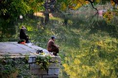 夫妇平静地坐跳船和鱼在北京中国之外的一个湖 免版税图库摄影