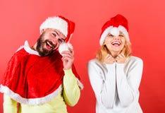 夫妇庆祝寒假圣诞晚会 人有胡子和妇女圣诞老人帽子红色背景 圣诞节化妆舞会 免版税库存图片