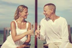 夫妇庆祝海滩夏天多士香宾概念 免版税库存照片