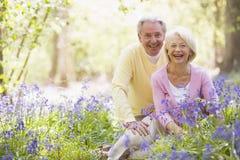 夫妇开花户外坐的微笑 免版税库存照片
