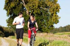 夫妇循环的跑步的体育运动年轻人 免版税库存图片