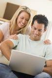 夫妇微笑膝上型计算机的客厅使用 库存照片