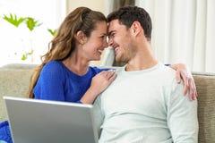 年轻夫妇微笑面对面在沙发和使用膝上型计算机 库存照片