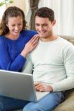 年轻夫妇微笑面对面在沙发和使用膝上型计算机 图库摄影