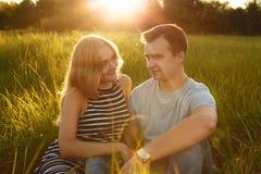 夫妇愉快室外 放松在绿草的微笑的夫妇 女孩和男孩在自然绿色背景 好关系 r 免版税库存照片