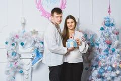 夫妇愉快拥抱怀孕 圣诞节概念 库存图片