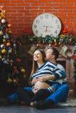 夫妇愉快拥抱怀孕 圣诞节概念 免版税图库摄影