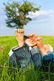 夫妇愉快的位于的草甸 免版税库存图片
