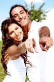夫妇愉快的指向的年轻人 免版税库存图片
