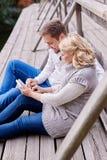 年轻夫妇愉快的放松在长凳的丈夫和怀孕的妻子 图库摄影