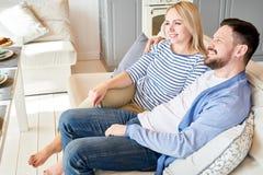 夫妇愉快的松弛沙发 免版税库存图片