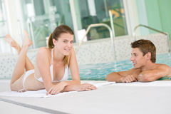 夫妇愉快的池放松游泳年轻人 免版税库存照片