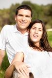 夫妇愉快的纵向坐的微笑的年轻人 免版税库存照片