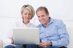 夫妇愉快的膝上型计算机成熟工作 免版税图库摄影