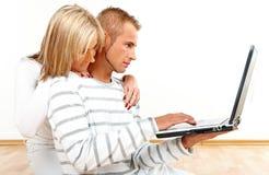 夫妇愉快的膝上型计算机 免版税库存照片