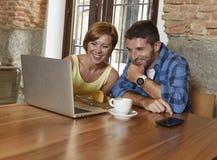 夫妇或朋友在咖啡店与便携式计算机一起使用在愉快的早晨 免版税库存图片