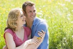 夫妇户外坐微笑的花藏品 免版税库存照片