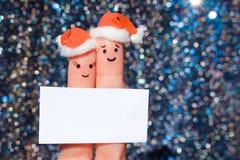 夫妇手指艺术庆祝圣诞节 笑在新年帽子的男人和妇女的概念 免版税库存图片