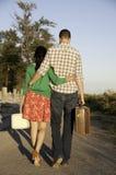 夫妇手提行李走 免版税库存图片