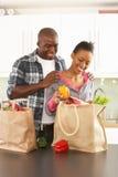 夫妇打开年轻人的厨房购物 库存图片