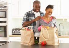 夫妇打开年轻人的厨房购物 免版税库存照片