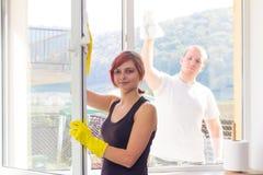 年轻夫妇打扫灰尘窗口在家 库存照片