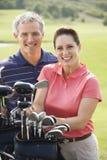 夫妇打高尔夫球演奏纵向微笑 免版税库存图片