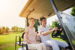 夫妇打高尔夫球 一个人在一辆白色高尔夫球汽车的轮子后坐,妇女坐近 免版税图库摄影