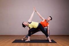 夫妇执行延长的侧角瑜伽伙伴姿势系列  免版税库存图片