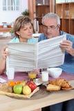 夫妇报纸读取 库存图片