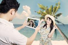 夫妇拍照片在海滩 免版税库存图片