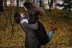 夫妇拥抱在秋天公园 在背景的金黄秋天与叶子和树,叶子 库存照片