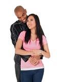 夫妇拥抱微笑的年轻人 库存照片