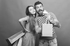 夫妇拥抱,拿着在绿色背景的购物袋 免版税库存照片
